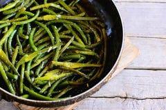 Flèches frites d'ail avec des épices dans une poêle et sur une vieille table en bois Nourriture végétale facile et saine Photos stock