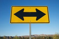 Flèches noires sur le panneau routier jaune Image libre de droits