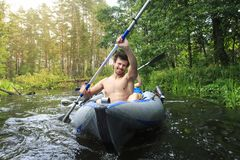 Flößen in einem Kanu durch den Fluss Junge Kerle mit Rudern in einem Boot segeln auf den Fluss im Sommer stockfotografie