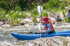 Flößen, fahrend Kayak Segeln des jungen Mädchens auf einem aufblasbaren Gummiboot in einem stürmischen Strom des Wassers Wasser s Lizenzfreies Stockbild