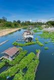 Flößen Sie Häuser mit grünes eco sich hin- und herbewegenden Bauernhöfen in einem Fluss von Thailand Stockfotos