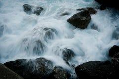 flöda över rocks som rusar vatten Arkivfoto
