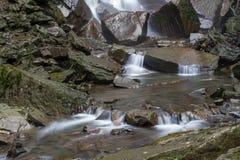 flöda över stenvatten Vid grunden av vattenfallet Arkivfoto