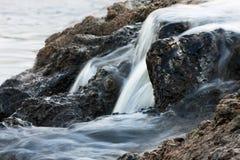 Flödande över stenar för vatten Arkivfoto
