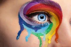Flödande färger på ett öga i modeetapp utgör Royaltyfri Foto
