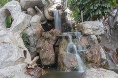 Flödande rörelse för vattenfall på stenen i trädgården Arkivfoton