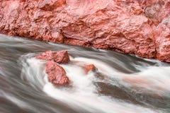 Flödande vatten runt om röda stenar Arkivbild