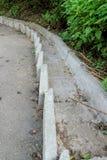 Flöde för konkret moment för flödet av regnvatten längs en mycket brant asfaltgångbana som kör ner kullen royaltyfri fotografi