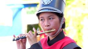 Flöjtistkvinna som spelar pickolaflöjten och marschmusikbandet lager videofilmer