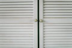 Flöjtlika vita träskåpdörrar i köknärbilden arkivbild