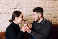 Flörta i ett kafé Härliga älska par som sitter i kafét som tycker om i coffe och konversation royaltyfria foton