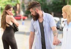 Flörta i gatan Förälskelsetriangel och threesome Man som fuskar hans flickvän Skäggig man som ser annan flicka royaltyfri fotografi