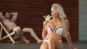 Flörta kvinnan som dricker coctailen nära simbassäng Modernt koppla av för par stock video
