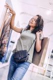 Flörtkvinnashopping i kläderboutique arkivfoto