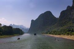 Flösse und Boote mit den Touristen, die in Li River nahe der Stadt von Yangshuo in China kreuzen stockbild