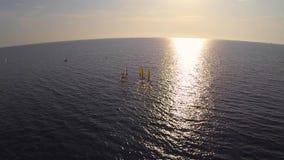 Flöte för fyra surfare in mot solnedgången arkivfilmer