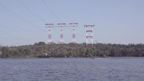 Flöten för motoriskt fartyg på floden mot bakgrunden av denspänning maktöverföringen står högt arkivfilmer