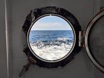 Flüchtiger Blick durch eine Öffnung in einer alten Fähre, zum der Wellen des Ozeans und des Himmels zu sehen lizenzfreie stockfotografie