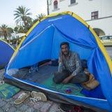 Flüchtling, der in einem Zelt sitzt und an einem Handy spricht Lizenzfreies Stockfoto