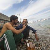 Flüchtling rasiert den anderen auf dem Strand Viele Flüchtlinge kommen aus der Türkei in aufblasbare Boote Stockfotografie