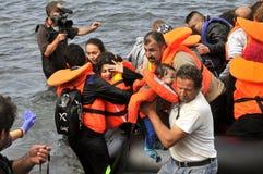 Flüchtlinge, die in Griechenland im schmuddeligen Boot von der Türkei ankommen Stockfotos