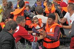 Flüchtlinge, die in Griechenland im schmuddeligen Boot von der Türkei ankommen Lizenzfreie Stockfotografie