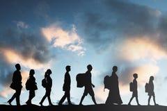 Flüchtlings-Leute mit Gepäck in Folge gehend stockfotografie