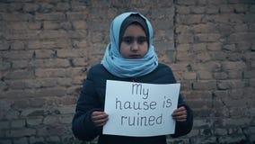 Flüchtlingsmädchen mit einer Aufschrift auf einem weißen Blatt stock video