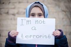 Flüchtlingsmädchen mit einer Aufschrift auf einem weißen Blatt lizenzfreies stockbild
