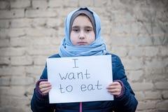 Flüchtlingsmädchen mit einer Aufschrift auf einem weißen Blatt stockbilder
