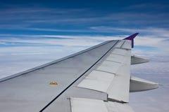 Flügel der Fläche in der Wolke des blauen Himmels wenn Blick heraus das Fenster Stockfotografie