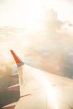 Flügel des Flugzeuges auf Wolkenhimmel vom Fenster am Morgen Lizenzfreies Stockfoto