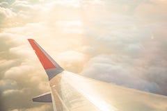 Flügel des Flugzeuges auf Wolkenhimmel vom Fenster am Morgen Stockfotos