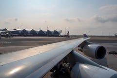 Flügel des Flugzeuges geparkt im Flughafen auf Wolkenhimmelhintergrund lizenzfreies stockfoto