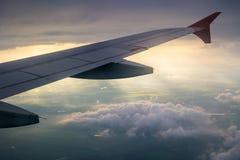 Flügel des Flugzeuges vom Fenster mit schönem Sonnenlicht und Wolke Lizenzfreie Stockfotos