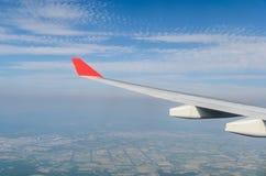 Flügel des Flugzeugfliegens über dem Land Stockbild