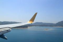 Flügel des Flugzeugfliegens über dem Meer und dem Strand Stockfotografie