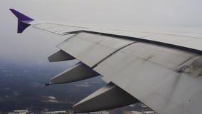 Flügel des Flugzeugfliegens im Himmel bei der Landung am Flughafen stock footage