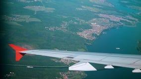 Flügel einer Flugzeugansicht vom Fenster des flachen Fliegens über der Stadt und dem Fluss Flugzeug-Flug Vorbei reisen stock footage