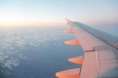 Flügel eines Flugzeugfliegens über dem Sonnenaufgang bewölkt sich Stockbilder