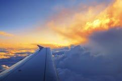 Flügel eines Flugzeugfliegens über dem Sonnenuntergang bewölkt sich Lizenzfreies Stockfoto