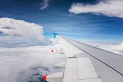 Flügel eines Flugzeugfliegens über Wolken Stockfotografie