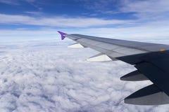 Flügel eines Flugzeugflugwesens über den Wolken Stockbilder