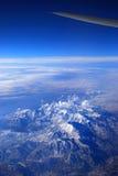 Flügel eines Passagierflugzeugs über den Bergen stockfotografie