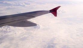 Flügel von Flugzeugen mit den schneeweißen clounds auf Hintergrund Lizenzfreie Stockfotografie