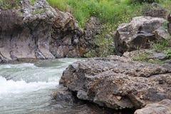 Flüsse eines Stromes zwischen die Felsen lizenzfreies stockbild