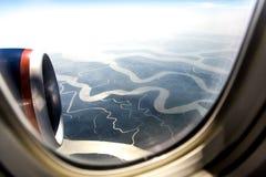 Flüsse und Himmel im Flugzeugfenster Stockfotografie