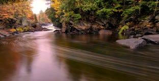 Flüssiger Fluss mit Fall-Farben Stockfotografie