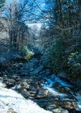 Flüssiger Fluss neben Snowbank Stockbild