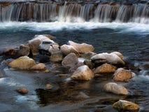 Flüssiger Fluss und Eis bereifte Steine Stockfotos